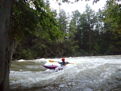 A kayaker surfs a hole on the Upper Big Sandy Creek