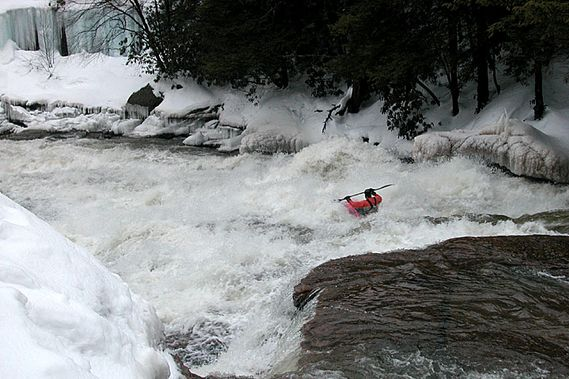 A kayaker goes over Swallow Falls in the winter