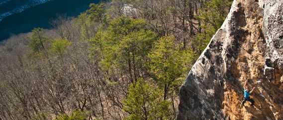 A climber high on a New River Gorge cliff