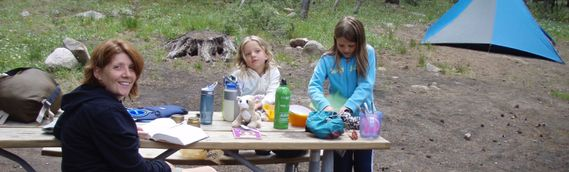 A family at the picnic table while camping