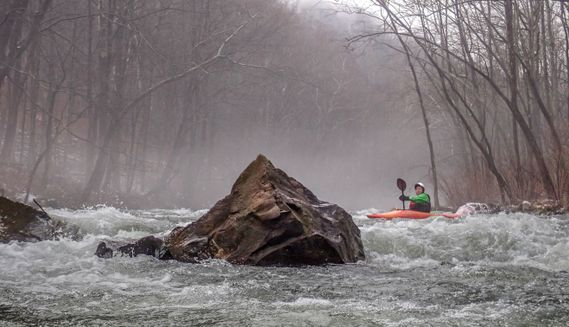 A kayaker paddles around a large rock on the Savage River