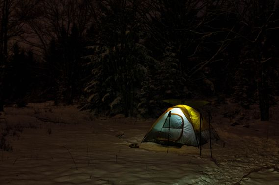 A tent is lit up in the winter darkness
