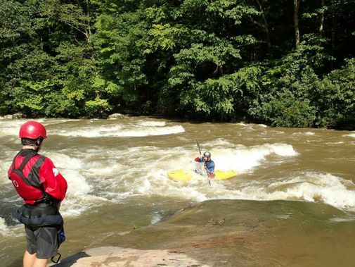 A son watches his father kayak through a rapid on Big Sandy Creek