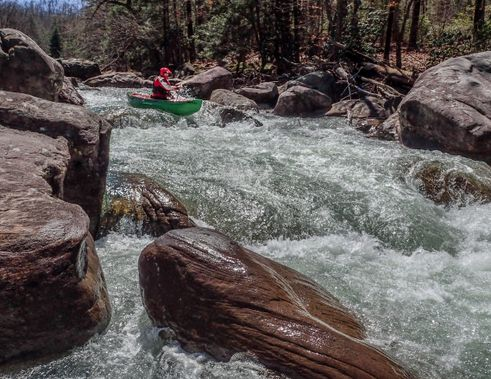 A canoer navigates a rapid on the Buckhannon River
