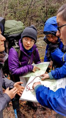 A group of backpackers checks their map