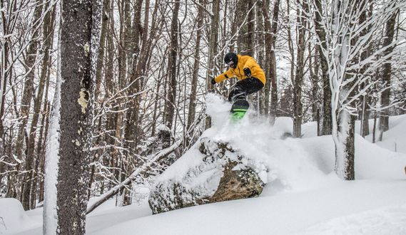 A snowboarder jumps off of a powder covered rock