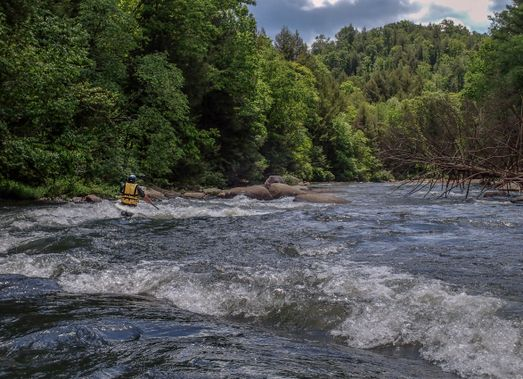 A kayaker paddles through a rapid on the Upper Big Sandy Creek