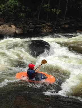 A younger kayaker going down the main drop in Calamity Rapid