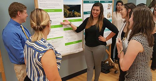A student presenting her research poster