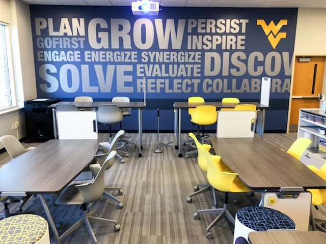 Tables and chairs in the active learning center with a mural as it's background