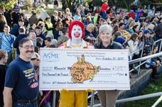 Ronald McDonald holding a large pumpkin check showing the donation being made to Ronald McDonald House.