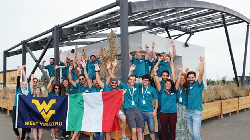 A photo of the University Tor Vergata and West Virginia University 2015 Solar Decathlon team standing in front of their fully built Solar house and waving both the WVU Flag and Italian Flag