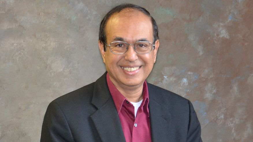 A portrait of Rakesh Gupta in a charcoal colored suit and a burgundy dress shirt.