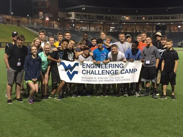 Engineering in Action 2015 Campers at Mountaineer Baseball Stadium holding WVU Engineering Challenge Camp banner