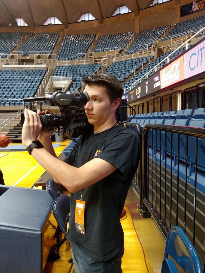 Trevor Gromen holding a shoulder camera at the WVU Coliseum.