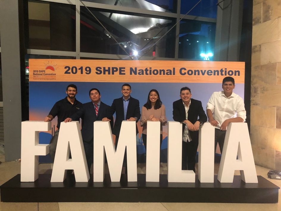 Students in the Society of Hispanic Professional Engineers at a conference standing in front of large letters that say familia.