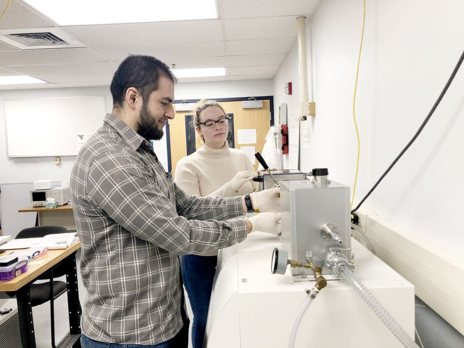 Graduate students in Song's research lab perform a measurement of electrical properties. (Submitted photo)