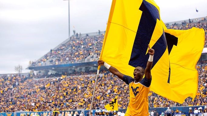 "Lionell Marshall carrying the ""W"" flag on the field at Mylan Puskar Stadium in Morgantown."