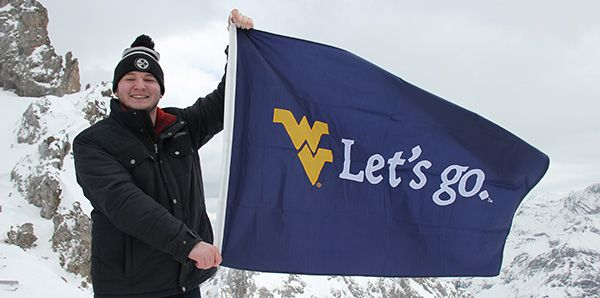 Male student on snowy mountain in Germany holding a WVU Let's Go flag.