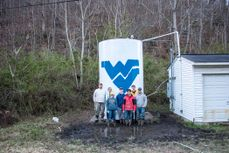 A photo of EWB members standing by a water tank with a Flying WV painted on it.
