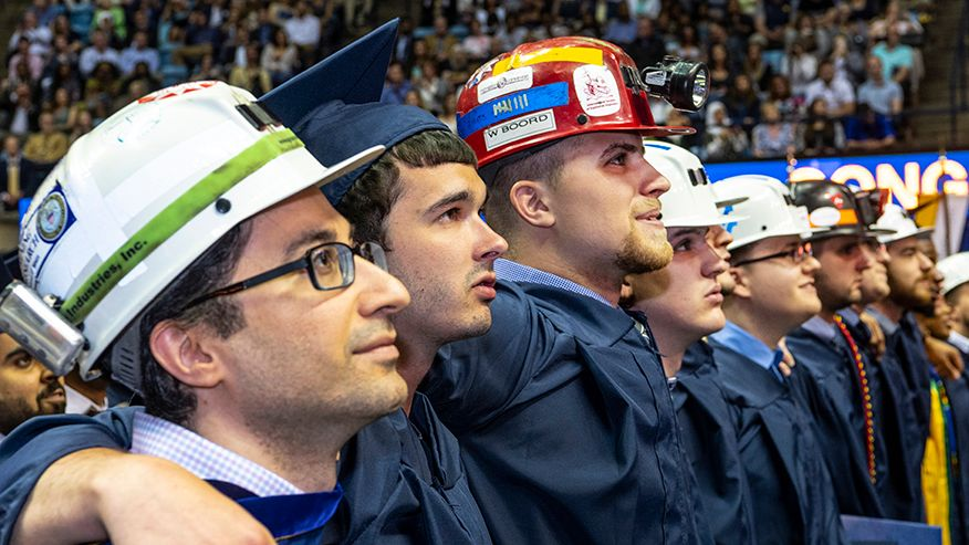 Graduates wearing hard hats at graduation.