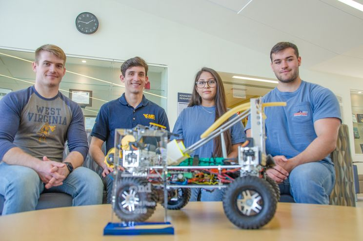 A photo of four students with a robot.