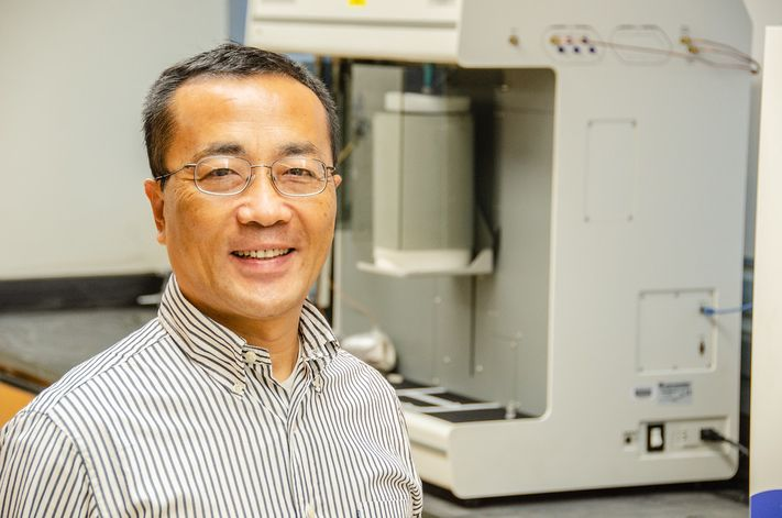A portrait of John Hu in his research lab