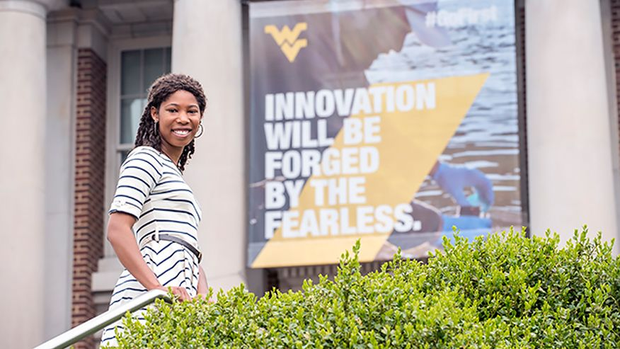 "Noelle Honey cut standing in front of a WVU sign ""Innovation will be forged by the fearless."""