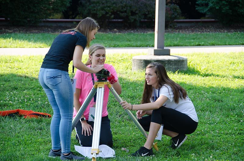 Three females working on camp engineering project.