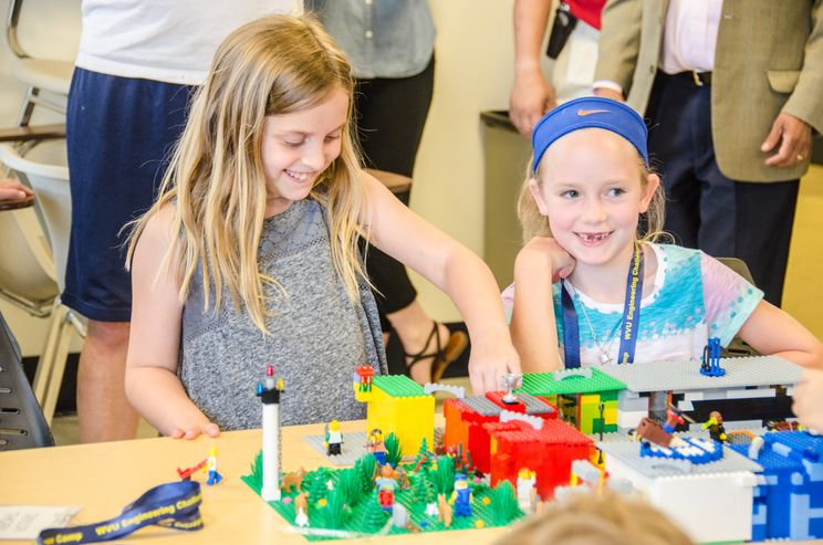 A photo of two girls building a city out of Legos.