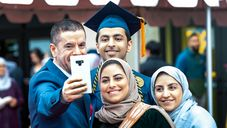 A family taking a selfie after the graduation ceremony.