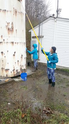 A photo of two EWB members standing in knee-deep water cleaning a tank.