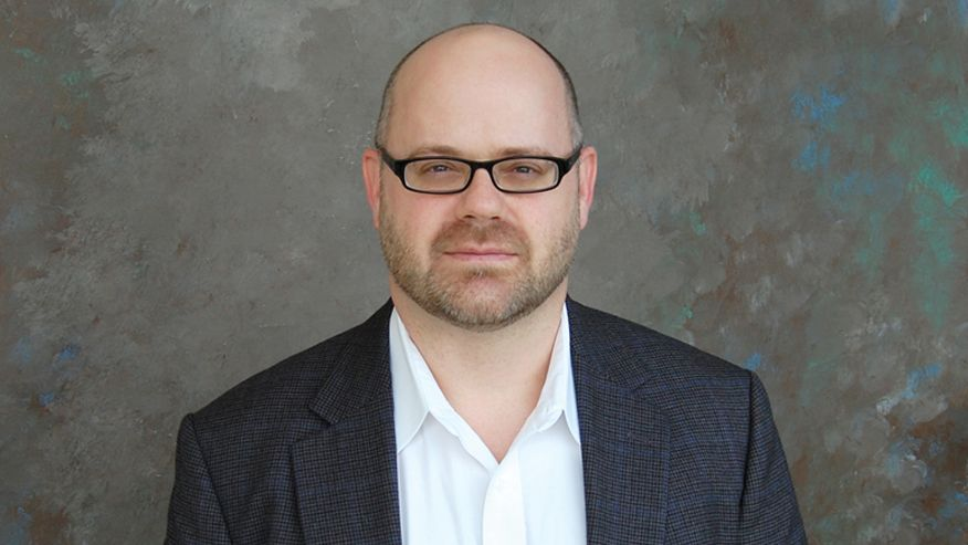 A portrait of Ed Sabolski from the chest up, wearing a black suit coat over a white dress shirt and a pair of rectangular, thick framed glasses