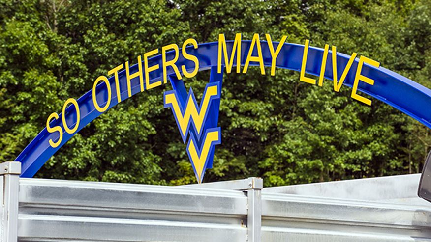 "An image of the Sago Mine entrance with a blue WVU sign above it with the words ""So others may live"" and a flying WV logo in gold"