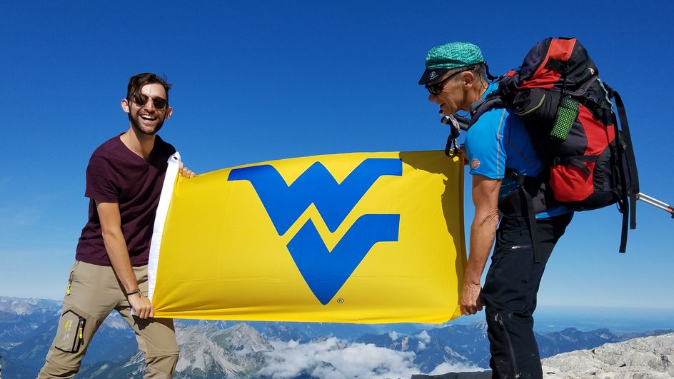 Jack Prommel holds a West Virginia University flag on peak of mountain in the Alps.