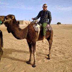 A photo of Tyler Hartman on a camel.