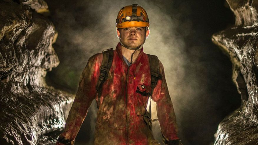 Ryan Maurer wears orange overalls and a yellow hard had with a head lamp, standing inside of a cave with two large rock walls on either side of him