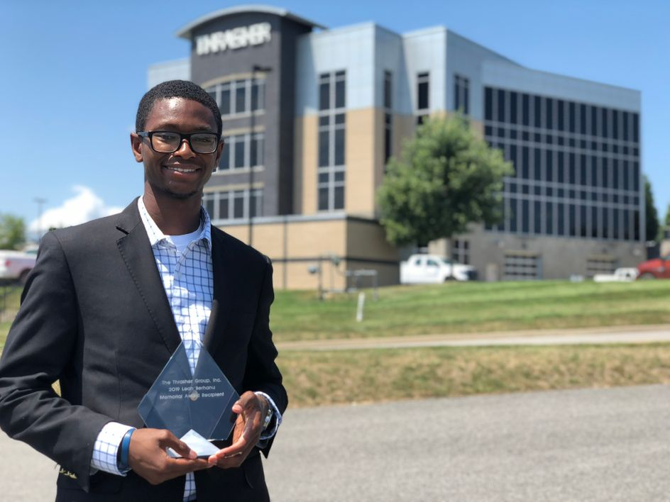 Torey Wright with his award in front of The Thrasher Group building
