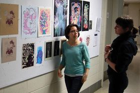 students viewing prints in hallway