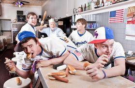 students posed in a diner eating hot dogs