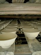 clay bowls drying on wooden beams