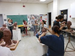 students carving clay heads
