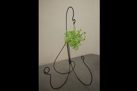metal holder with green sculpted plant