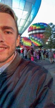 Eric Myers in front of hot air balloons.