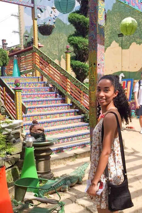 Oriana Ovide at Randyland in Pittsburgh, in front of multicolored steps.