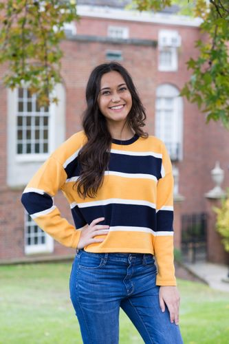 Photo of Natalie Rogers wearing gold and blue sweater.