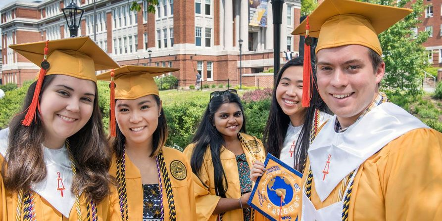 Five smiling WVU graduates in their Honors College gold robes.