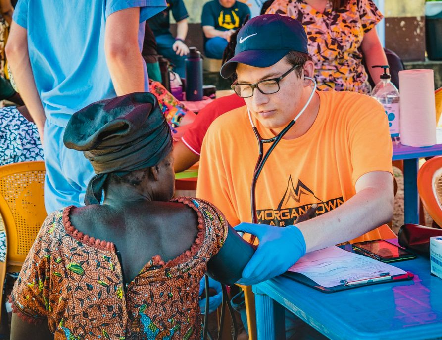 Nick Miller taking blood pressure for a community member in a small community in Ghana during one of their clinic days.