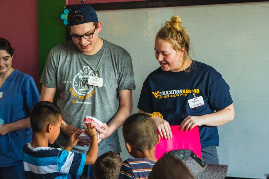 Nick Miller and other volunteers demonstrate for local children how to brush teeth on a dental model in a small community in Honduras.