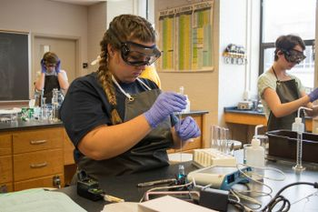 A student wears safety equipment to perform a chemistry lab experiment